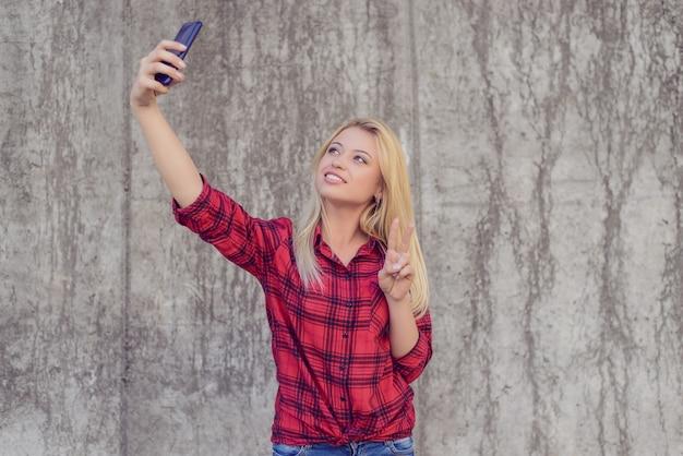Femme en vêtements décontractés avec un sourire rayonnant racontant un selfie sur son smartphone et montrant un signe v