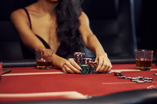 Femme en vêtements élégants est assis à cassino par table et joue au poker