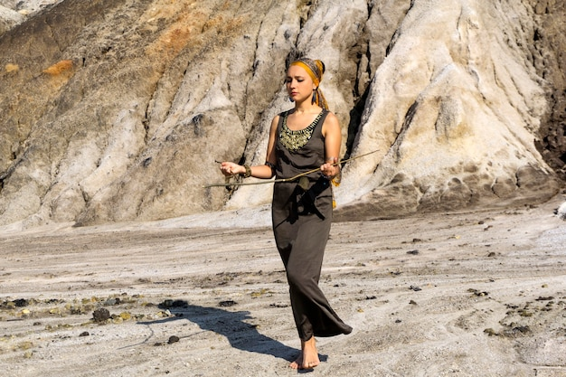 Une femme en vêtements ethniques orientaux cherche de l'eau dans une zone désertique par la méthode de radiesthésie