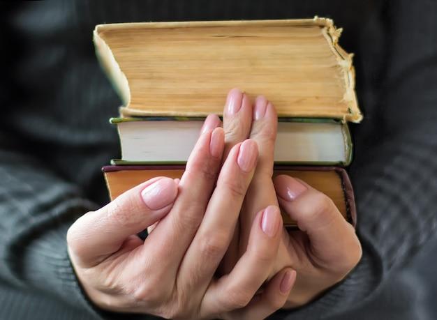 La femme en vêtements gris tient de vieux livres à la main
