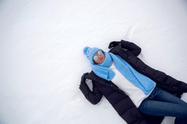 Femme en vêtements d'hiver allongé sur un lac gelé