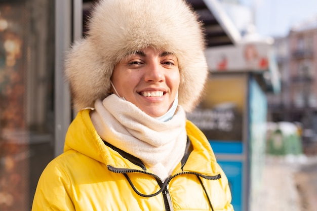 Femme en vêtements d'hiver par une journée froide en attente d'un bus à un arrêt de bus