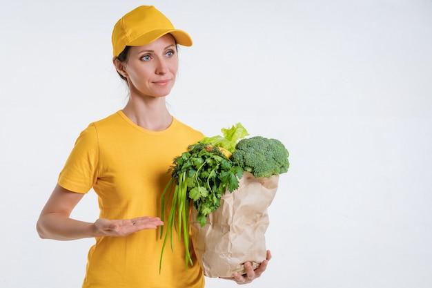 Une femme en vêtements jaunes, livrant un paquet de nourriture, sur fond blanc