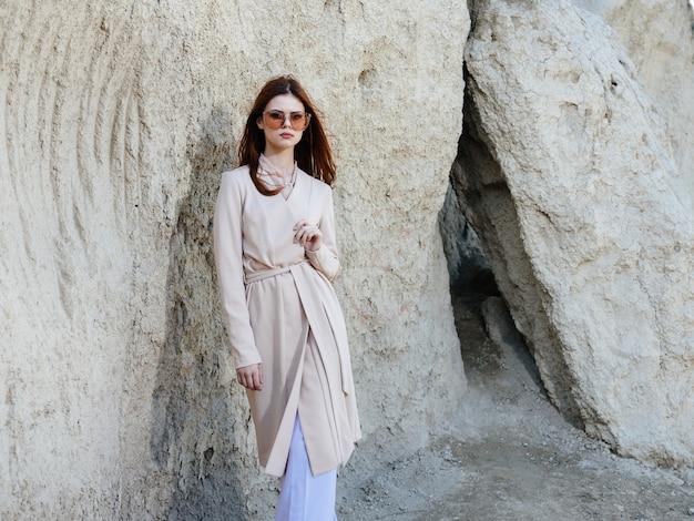Une femme en vêtements légers et près de grosses pierres dans la nature dans les montagnes