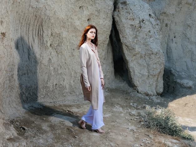 Femme en vêtements légers près des rochers dans la nature à l'extérieur