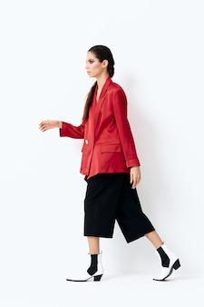 Femme en vêtements à la mode tient les mains près du visage posant le luxe.