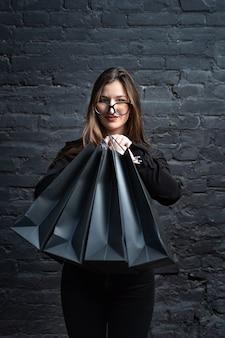 Femme en vêtements noirs détient des sacs en papier noir sur un mur sombre. cadre vertical.