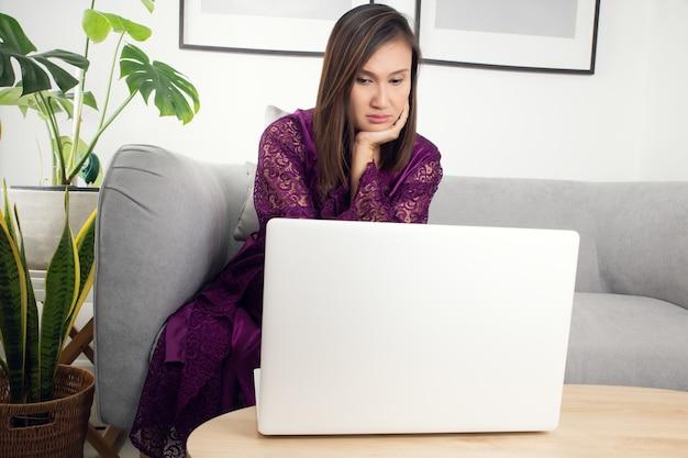 Femme en vêtements de nuit violet sur canapé-lit à l'aide d'un ordinateur portable dans une soirée sombre à la maison