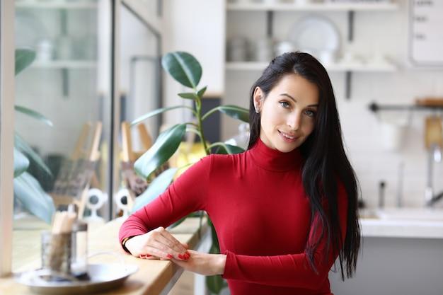 Femme en vêtements rouges est debout dans la cuisine