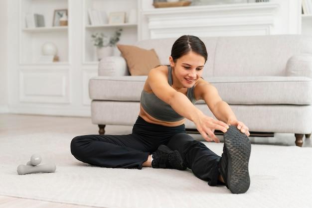 Femme en vêtements de sport faisant de l'exercice à la maison