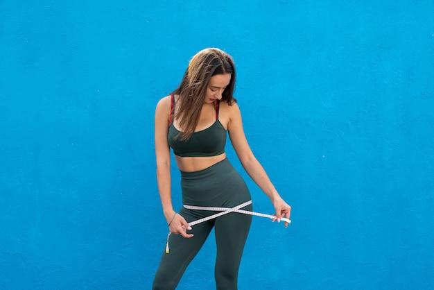 Une femme en vêtements de sport mesure son corps après l'entraînement. concept sain