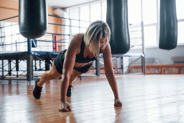 Femme en vêtements de sport noirs ont un exercice de planche sur le sol de la salle de gym.