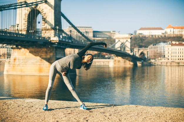 Femme en vêtements de sport s'étirant sur la promenade du danube à budapest