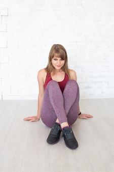 Femme en vêtements de style sport assis sur le sol.