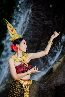 Une femme vêtue d'une ancienne robe thaïlandaise à la cascade.