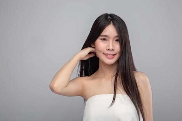 La femme vêtue de bretelles blanches et ses mains touchent ses cheveux.