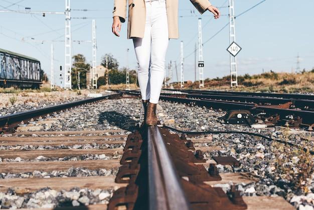 Femme vêtue d'un chapeau beige et d'une veste marchant le long des voies ferrées