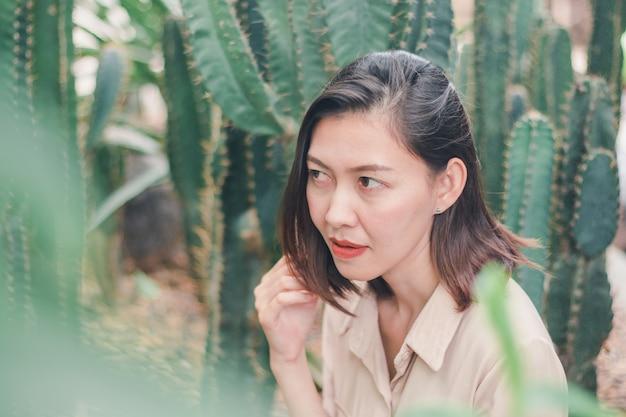 Une femme vêtue d'une chemise brune assise avec un cactus