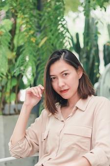 Une femme vêtue d'une chemise brune assise sur une chaise blanche