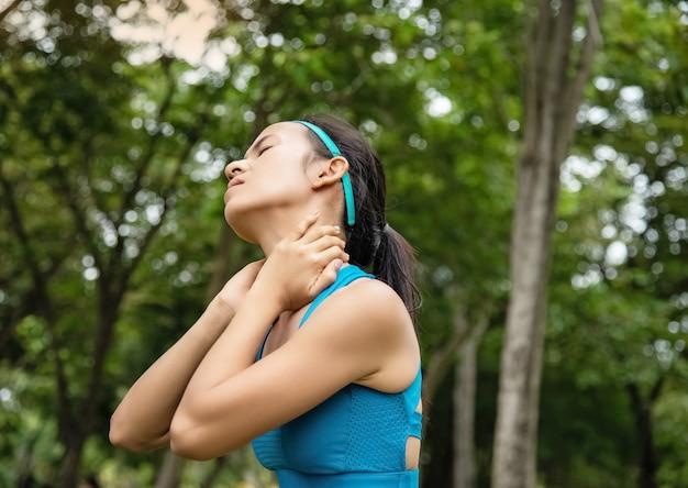 Femme vêtue d'une combinaison d'exercices, posez les mains sur son cou
