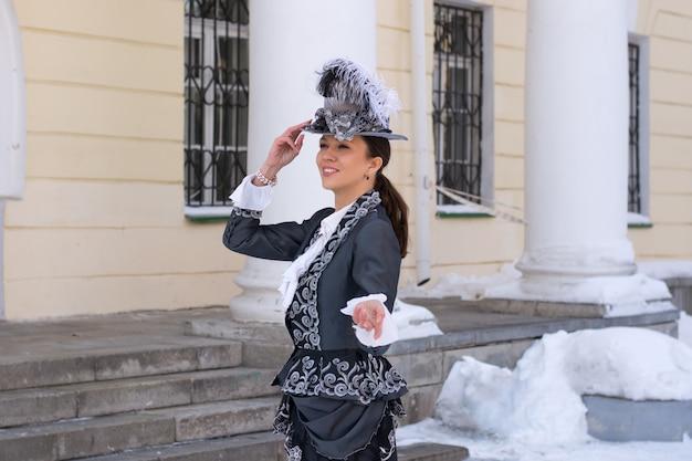 Une femme vêtue comme une noble du 19e siècle se tient près d'un vieux manoir.hiver russe