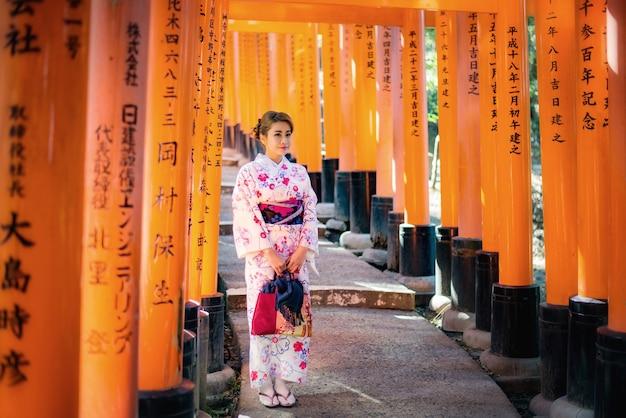 Femme vêtue d'un costume traditionnel japonais marchant sous les portes tori au sanctuaire fushimi-inari, kyoto japon