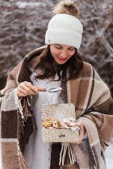 Une femme vêtue d'hiver tient une boîte avec des biscuits traditionnels russes en bois de broussailles photo de haute qualité