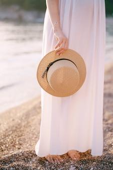 Une femme vêtue d'une longue robe blanche se tient sur la plage et tient un chapeau à la main