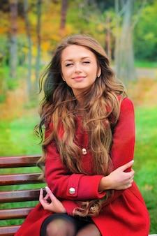Femme vêtue d'un manteau rouge assis dans le parc en automne.