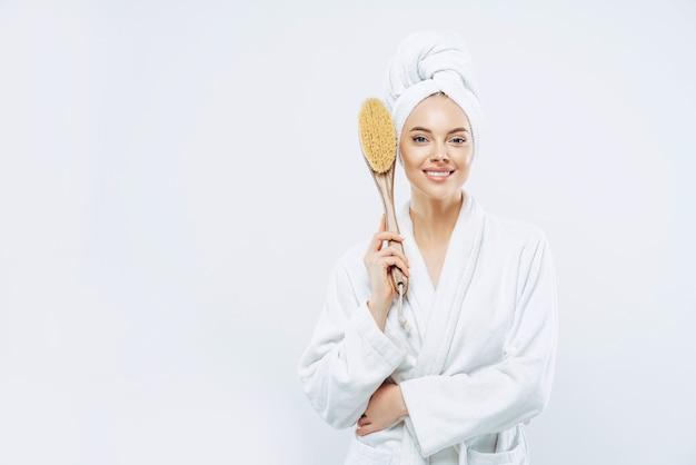 Femme vêtue de peignoir détient une brosse de massage anticellulite