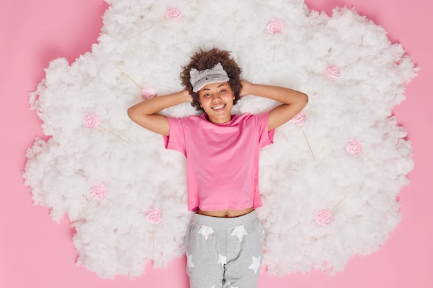 Femme vêtue d'un pyjama garde les mains derrière la tête sourit joyeusement se sent rafraîchie après avoir vu des rêves agréables et des poses de sommeil sur un nuage blanc