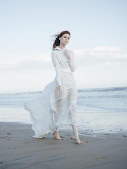 Une femme vêtue d'une robe blanche marche le long du rivage de l'océan le luxe de la liberté. photo de haute qualité