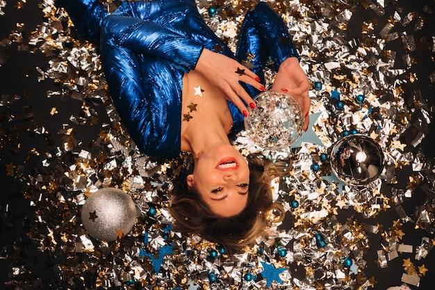 Une femme vêtue d'une robe bleue à paillettes sourit et s'allonge sur le sol sous une chute de confettis multicolores.