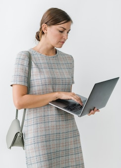 Femme vêtue d'une robe à carreaux grise à l'aide d'un ordinateur portable