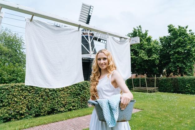 Femme vêtue d'une robe hollandaise traditionnelle, vêtements suspendus sur une corde à linge