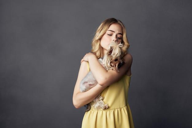 Femme vêtue d'une robe jaune avec un petit chien de race pure studio fond sombre