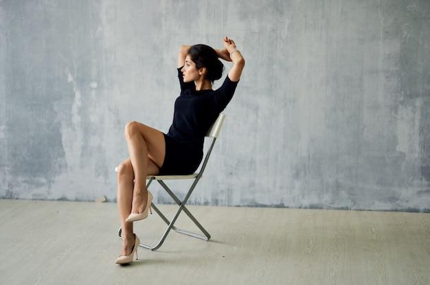 Une femme vêtue d'une robe noire est assise sur une chaise posant studio moda luxe
