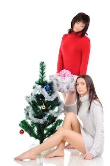 Une femme vêtue d'une robe rouge est assise par terre près d'un sapin de noël. fille dans une robe grise posant avec un cadeau dans ses mains