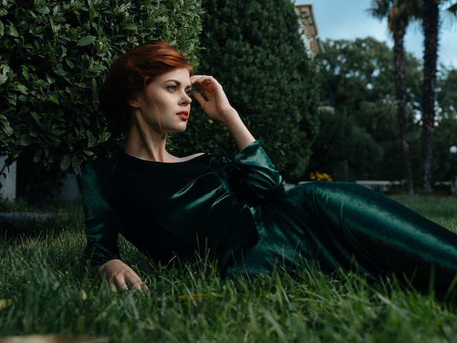 Une femme vêtue d'une robe verte se trouve sur l'herbe dans un jardin de fées