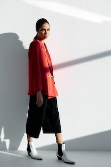 Une femme vêtue d'une veste rouge et d'un pantalon à la mode appuyé contre le mur, chaussures d'automne, bottes