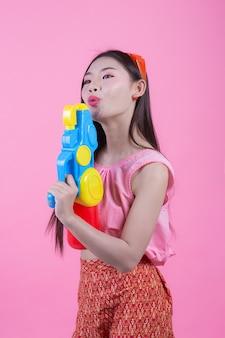 Une femme vêtue d'un vêtement traditionnel thaïlandais tenant un pistolet à eau sur un fond rose.
