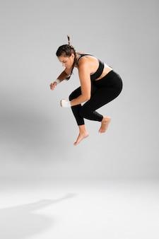 Femme vêtue de vêtements de fitness sautant