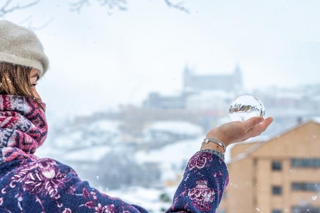 Femme vêtue de vêtements d'hiver tenant une boule de cristal dans un paysage urbain enneigé.