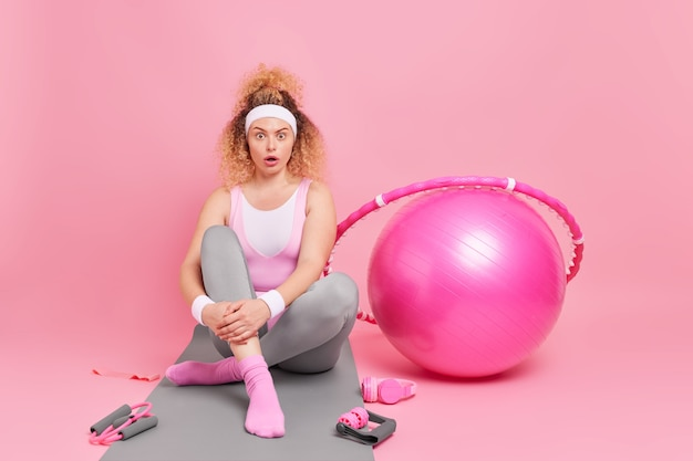 Une femme vêtue de vêtements de sport pose sur un tapis de fitness porte des exercices de bracelet avec bandeau fitball hula hoop s'entraîne au pilates dans des poses de gym
