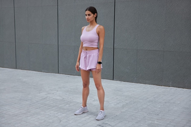 Une femme vêtue de vêtements de sport a des poses d'entraînement physique contre un mur gris porte une montre intelligente attend avec impatience des exercices à l'extérieur