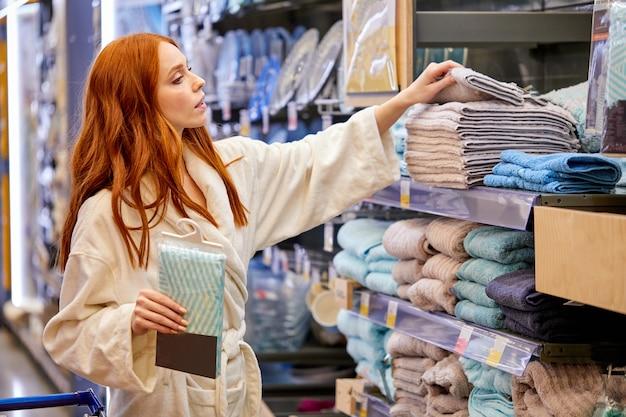 Femme veut acheter une serviette, femme porte un peignoir, dans l'allée d'un supermarché