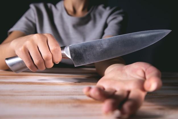 Une femme veut couper les veines avec un couteau de cuisine