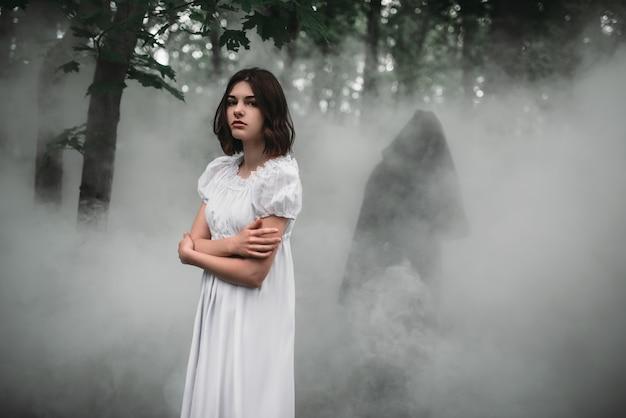 Femme victime en robe blanche dans la forêt brumeuse