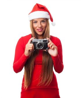 Femme avec un vieil appareil photo et le chapeau de père noël