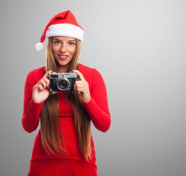 Femme avec un vieil appareil photo dans un fond gris